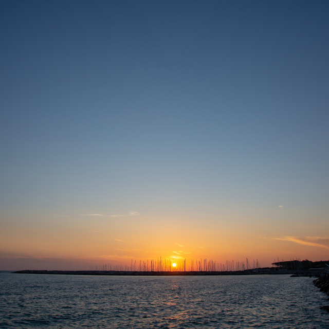 """""""Sunset in Cecina Italy over the sea behind stone breakwater"""" stock image"""