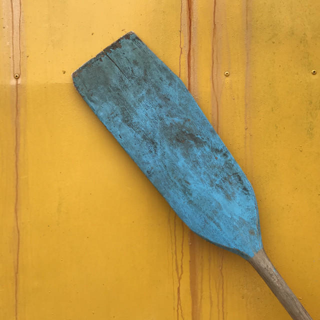 """Blue paddle on yellow wall"" stock image"