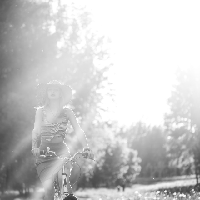 """Silhouette of girl driving bicycle outdoor. Sunny summer lifestyle concept...."" stock image"