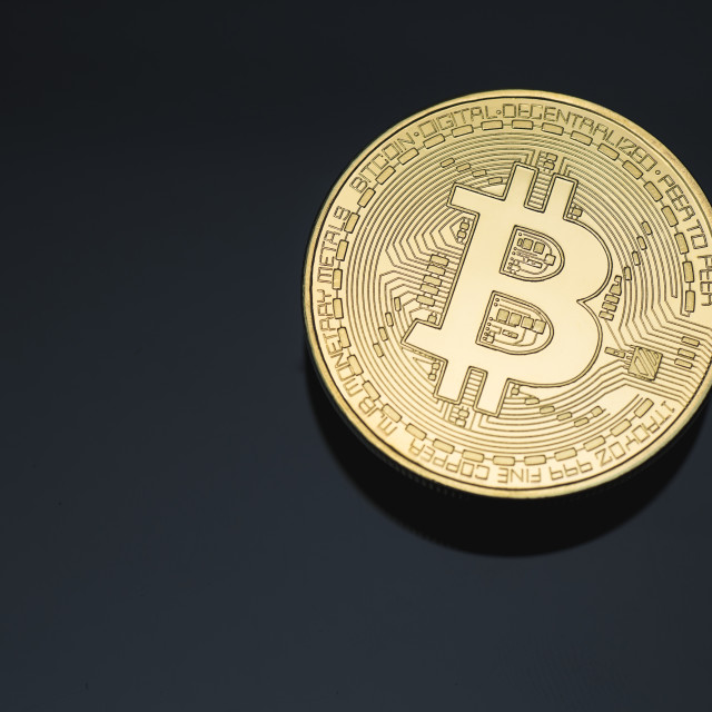 """Bitcoin cryptocurrency coin token close up cleaned golden gold macro with black background and copy space selective focus."" stock image"