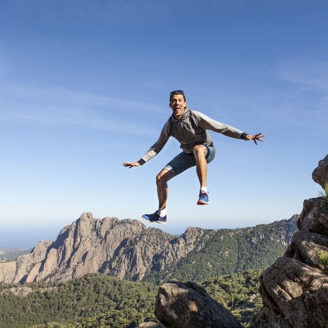 """man jumping above the mountains"" stock image"