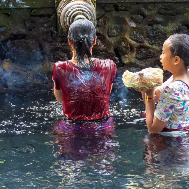 """Unidentified woman praying and doing purification ritual at the holy spring water at Pura Tirta Empul temple."" stock image"