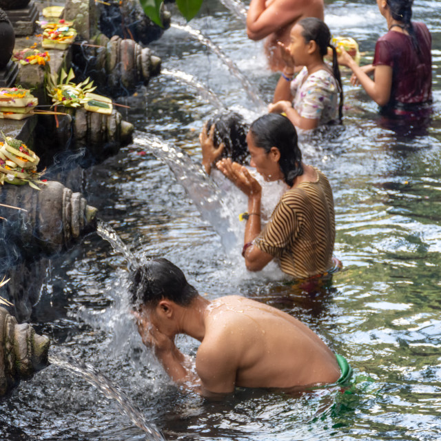 """People praying and doing purification ritual at the holy spring water at Pura Tirta Empul temple."" stock image"