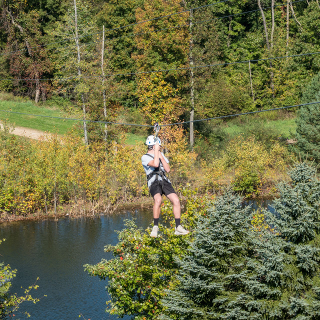 """""""Side view of a man on a zipline going down a valley in forest"""" stock image"""