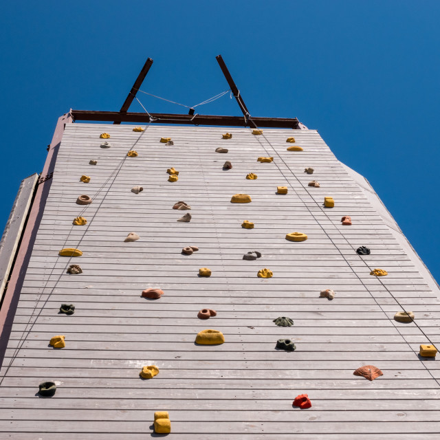 """View up to top of a high artificial climbing wall"" stock image"