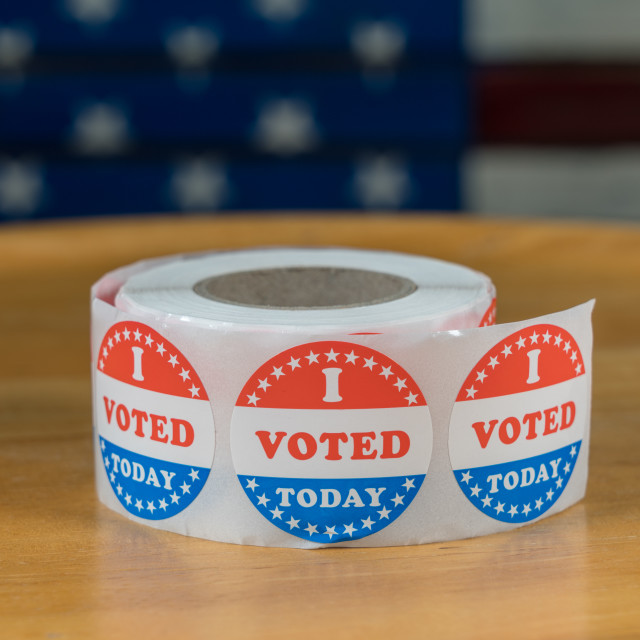 """""""Roll of I Voted Today paper stickers on table with US Flag in background"""" stock image"""