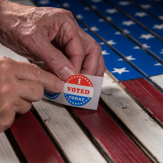 """""""Roll of I Voted Today paper stickers on US Flag with hand removing one"""" stock image"""