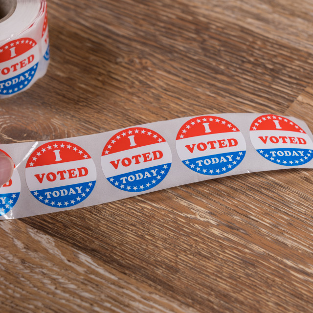 """""""Roll of I Voted Today paper stickers on table with senior man hand"""" stock image"""