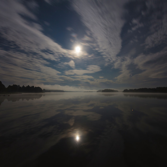 """""""Clouds in the night over the lake lit by full moon, long exposure shot"""" stock image"""