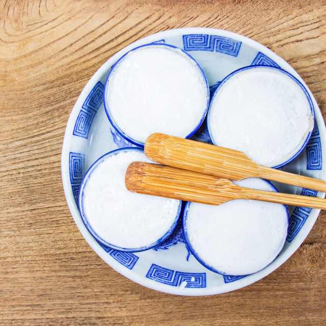 """""""Thai Coconut Milk Custard is a thai dessert made from rice flour, coconut milk and sugar put the small ceramic cups place are on a wooden floor. Khanom Thuai"""" stock image"""