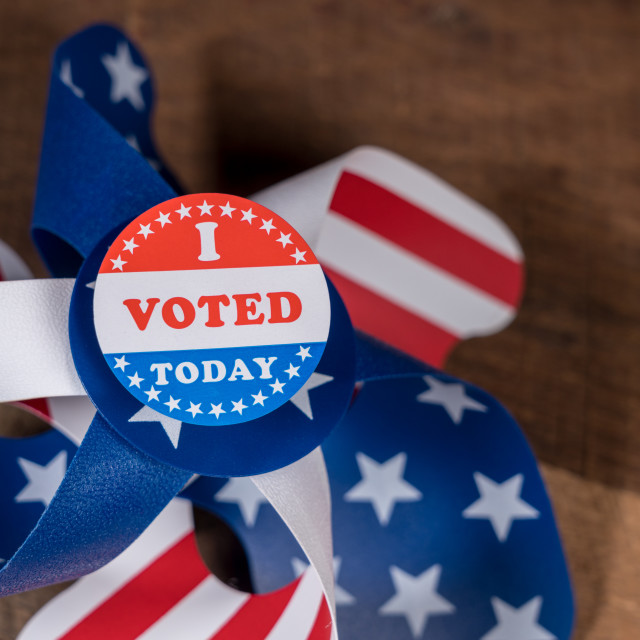 """""""I Voted Today paper sticker on US Flag whirligig and rural wooden table"""" stock image"""