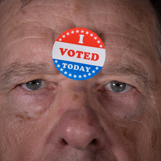 """""""I Voted Today paper sticker on mans forehead with angry stare at camera"""" stock image"""