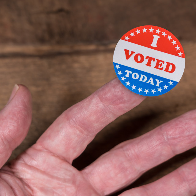 """""""I Voted Today paper sticker on mans finger on rustic wooden table"""" stock image"""