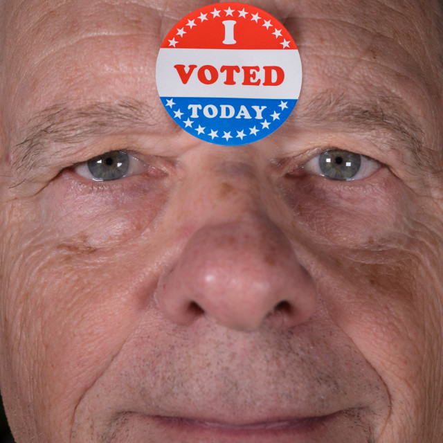 """""""I Voted Today paper sticker on mans forehead with warm smile at camera"""" stock image"""