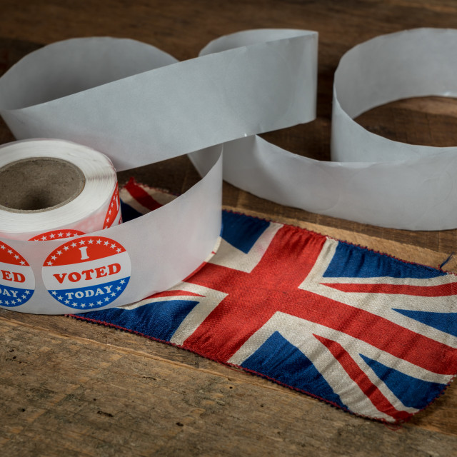 """""""Roll of I Voted Today paper stickers on table with UK Flag"""" stock image"""