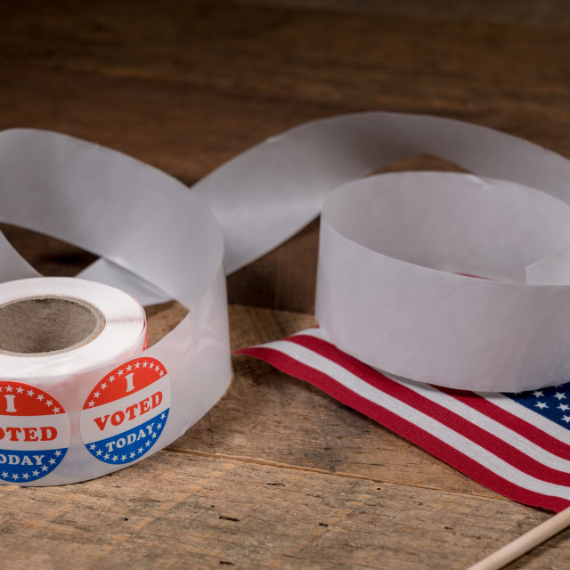 """""""Roll of I Voted Today paper stickers on table with US Flag"""" stock image"""