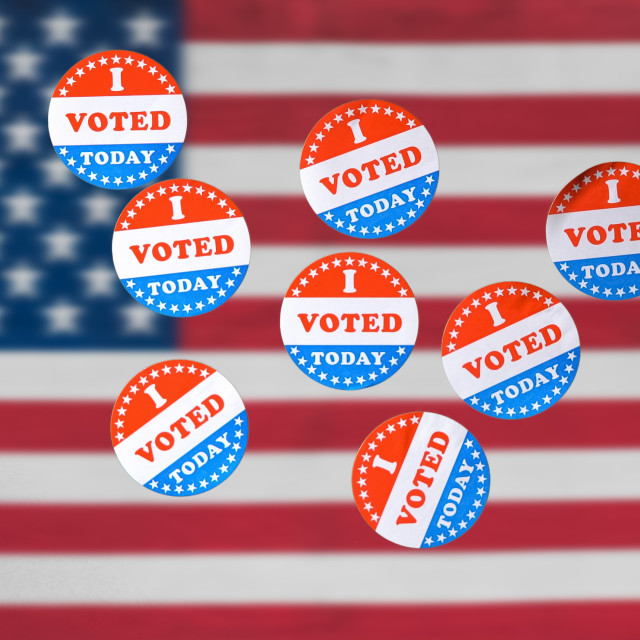 """""""Many I Voted Today paper stickers in front of US Flag in background"""" stock image"""