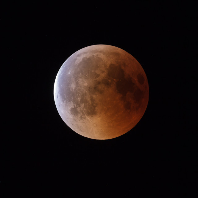 """""""Super Bloody Moon, beginning of full eclipse end phase against starry sky background"""" stock image"""