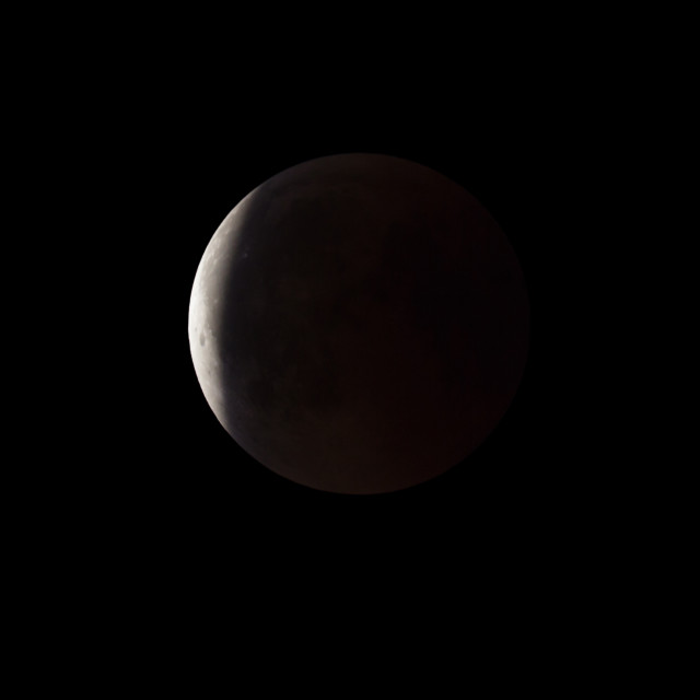 """""""Super Bloody Moon, full eclipse end phase against black sky background, Earth's shadow starting to move out from the Moon surface"""" stock image"""