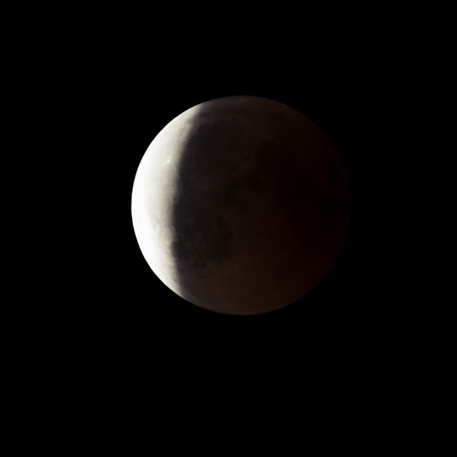 """""""Super Bloody Moon, full eclipse end phase against black sky background, three-quarters of the Moon surface covered by Earth's shadow"""" stock image"""