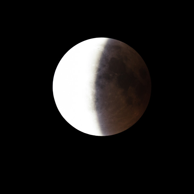 """""""Super Bloody Moon, full eclipse end phase against black sky background, half of the Moon surface covered by Earth's shadow"""" stock image"""