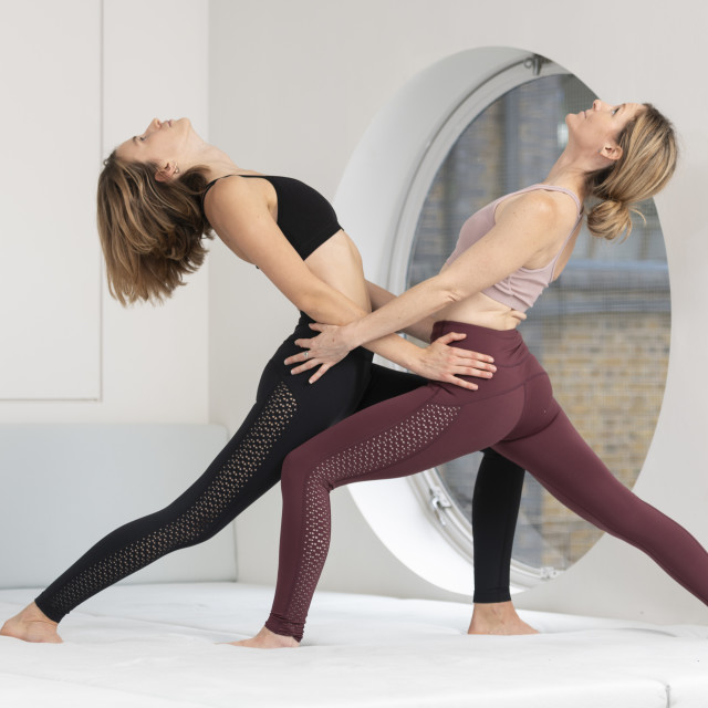 """two women practicing yoga together, acro yoga."" stock image"
