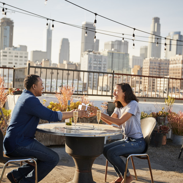 """Man Giving Woman Gift As They Celebrate On Rooftop Terrace With City Skyline..."" stock image"