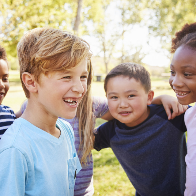 """Multi-ethnic group of schoolchildren laughing, outdoors"" stock image"