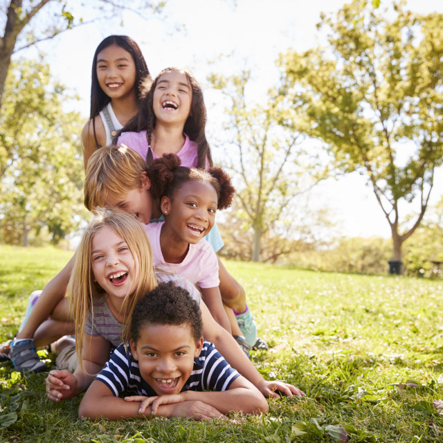 """Multi-ethnic group of children lying in a pile in a park"" stock image"