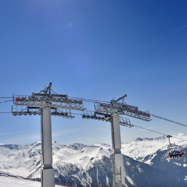 """poles and chair lift under sunny blue sky"" stock image"