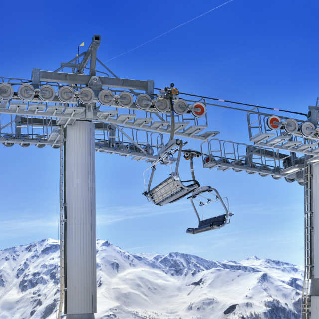 """poles and chair lift above snowy mountain"" stock image"