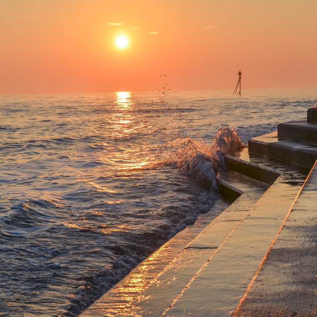 """""""Sunrise over sea wall"""" stock image"""