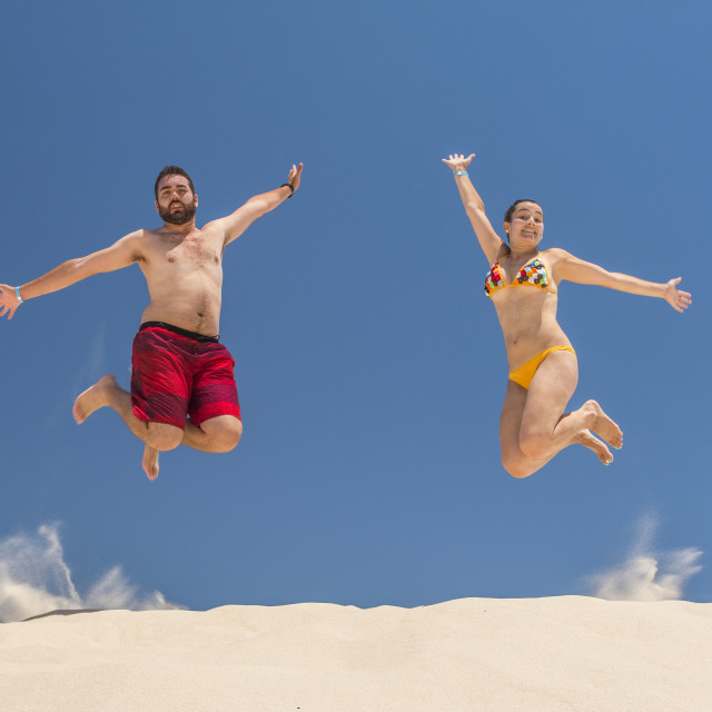 """""""Couple jumping at the beach"""" stock image"""