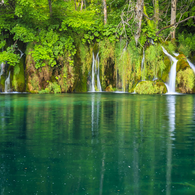 """""""Colorful panorama over waterfalls and a clear blue lake in a old green..."""" stock image"""