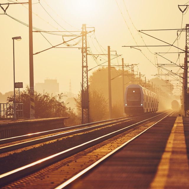"""Passenger train at sunrise."" stock image"
