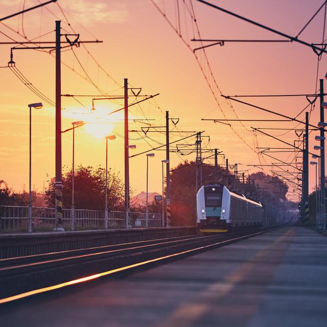 """Passenger train at sunrise."" stock image"
