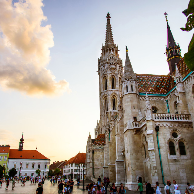 """""""Matthias Church in Budapest and the main square of the Buda Castle area crowded with tourists at sunset"""" stock image"""