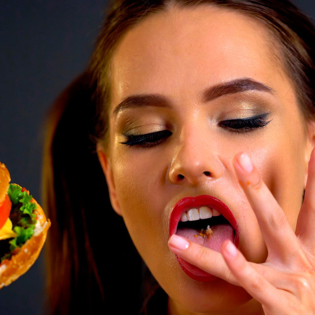 """Woman eating hamburger. Girl wants to eat fast food."" stock image"