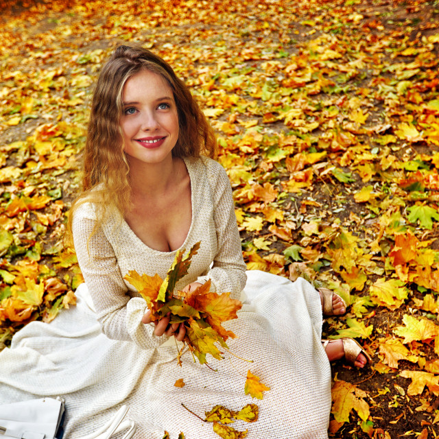 """""""Autumn fashion dress woman sitting fall leaves city park outdoor."""" stock image"""