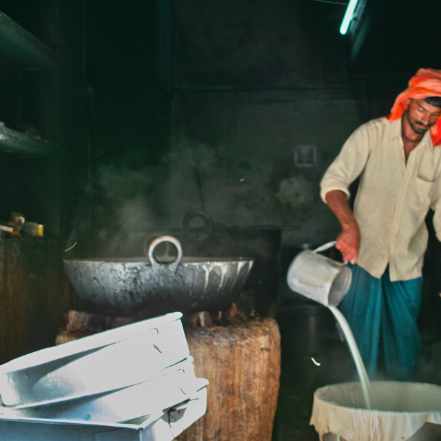 """Man making indian cheese (paneer) at a small factory"" stock image"