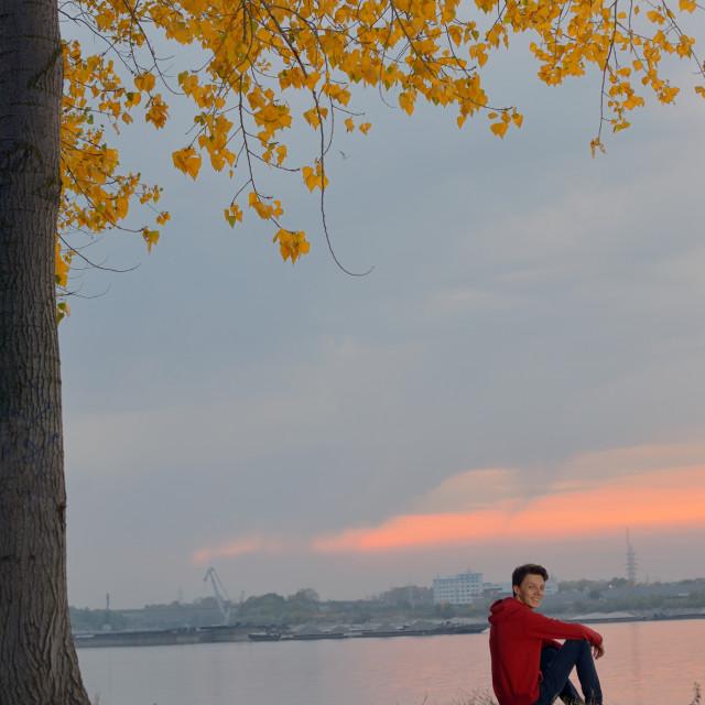 """Boy sitting at sunset"" stock image"
