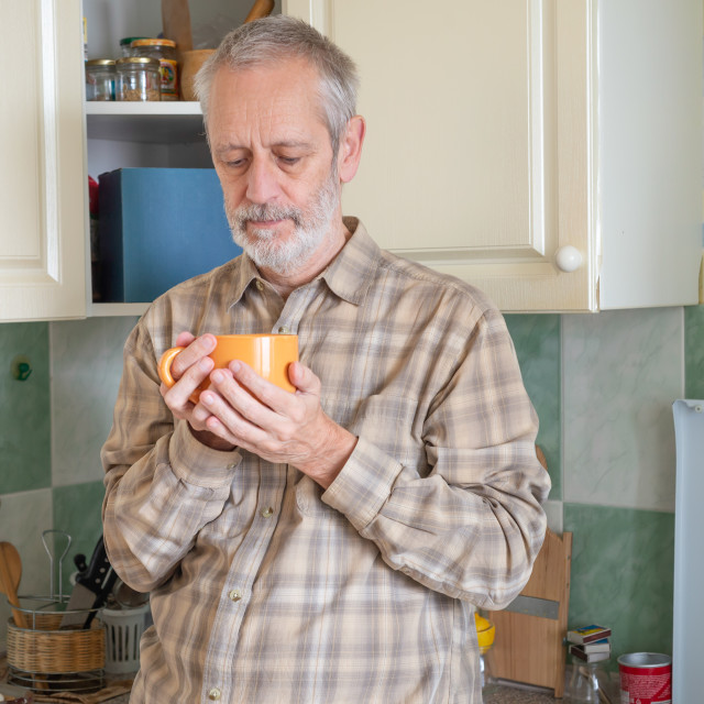 """Mature man drinking his coffee in kitchen"" stock image"