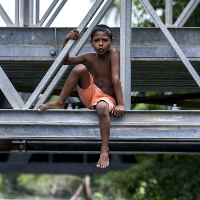 """A boy sits on a steel bridge."" stock image"