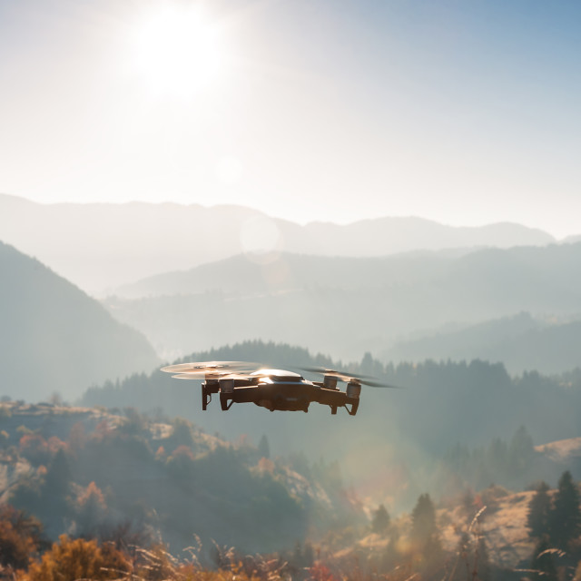 """""""Small modern drone hovering taking picture of sunrise in mountai"""" stock image"""