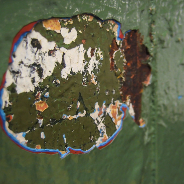 """""""Detail on rough urban wall with damaged hole in surface with exposed flaking layers of old weathered paint"""" stock image"""