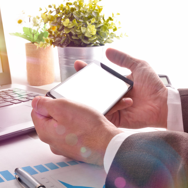 """""""Businessman watching multimedia content on a smartphone in an office"""" stock image"""