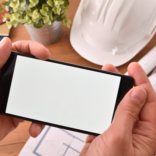 """""""Hands with smartphone watching multimedia construction content in an office"""" stock image"""