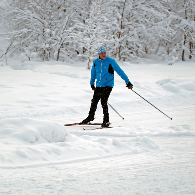 """A Skier glides across the snow"" stock image"
