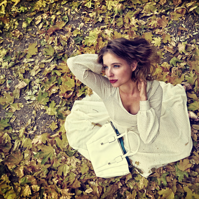 """Autumn fashion dress woman sitting fall leaves city park outdoor."" stock image"
