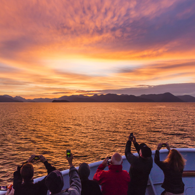 """Lindblad/National Geographic guests enjoying sunset at Chichagof Island,..."" stock image"